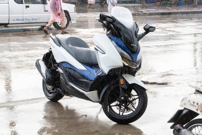 Vista laterale di parcheggio bianco-blu 2018 del motociclo di Honda Forza 300 sulla passeggiata laterale nella pioggia del giorno immagini stock