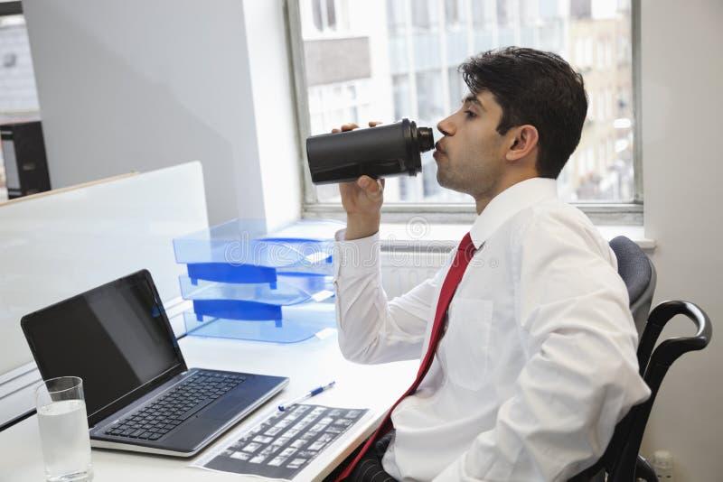 Vista laterale di un'acqua potabile dell'uomo d'affari indiano alla scrivania fotografia stock