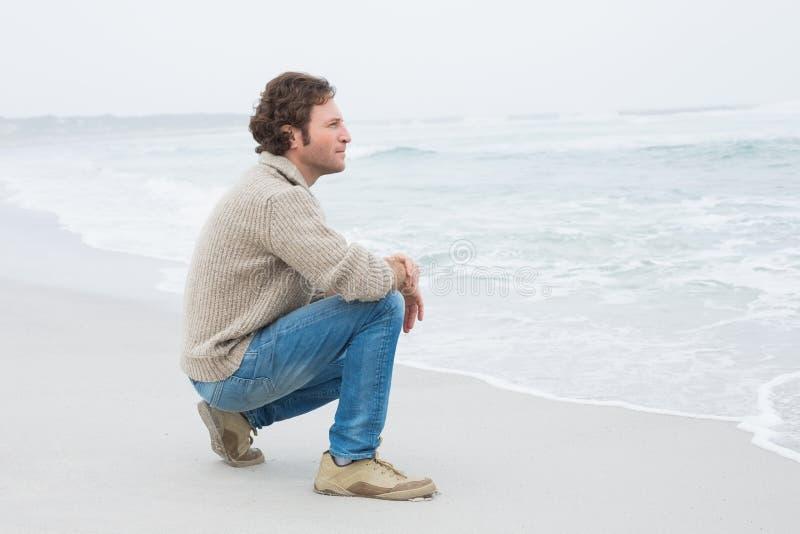 Vista laterale di un giovane casuale che si rilassa alla spiaggia fotografia stock libera da diritti
