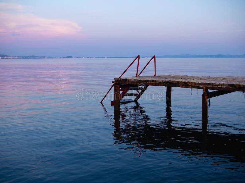 Vista laterale di un pilastro di legno sul mare al tramonto, Durres, Albania fotografia stock libera da diritti