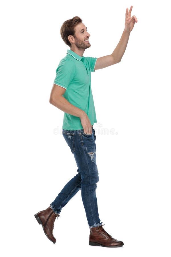 Vista laterale di un uomo che cammina mentre mostrando segno v immagine stock libera da diritti