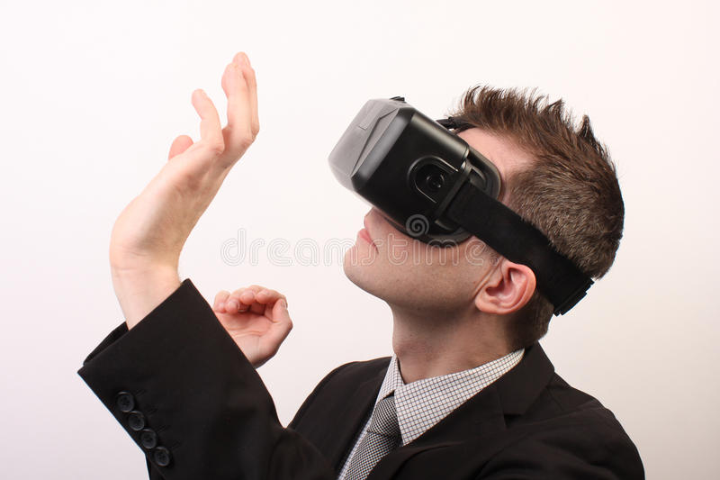 Vista laterale di un uomo che indossa una cuffia avricolare della spaccatura 3D dell'occhio di realtà virtuale di VR, toccando qu fotografia stock libera da diritti