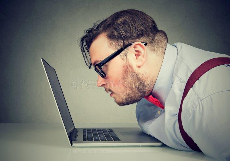 Vista laterale di un uomo con cattiva visione che incontra difficoltà per leggere email fotografia stock libera da diritti