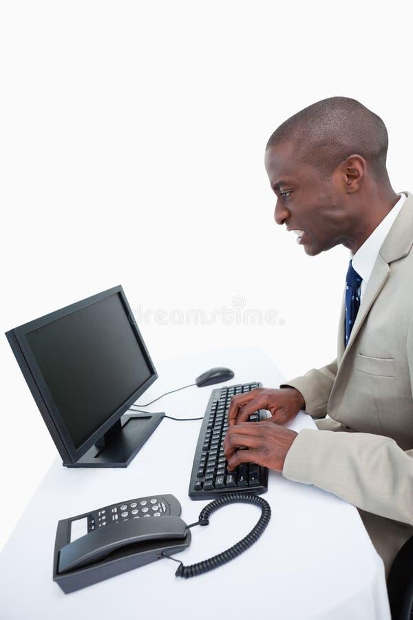 Vista laterale di un uomo d'affari arrabbiato facendo uso di un computer fotografie stock libere da diritti