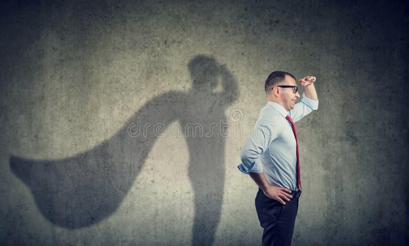 Vista laterale di un uomo d'affari che immagina essere un eroe eccellente che sembra aspirato immagine stock