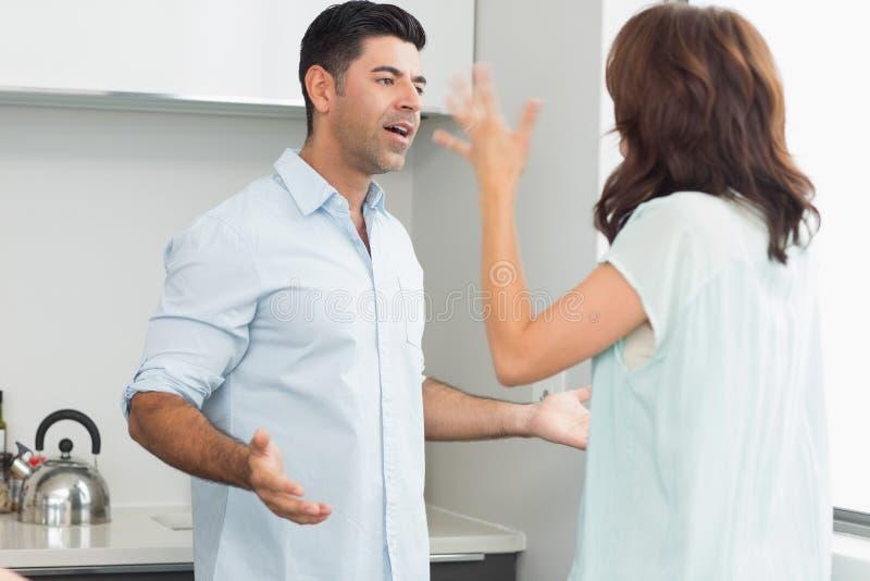 Vista laterale di una coppia che litiga nella cucina fotografia stock