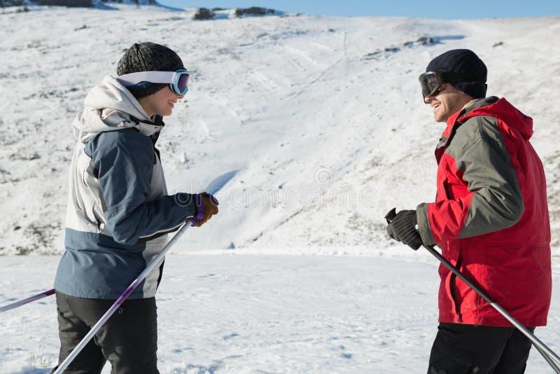 Vista laterale di una coppia sorridente con i pali di sci su neve fotografia stock libera da diritti