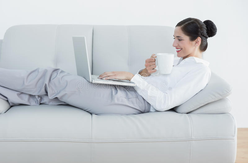 Vista laterale di una donna ben vestito con la tazza di caffè e del computer portatile sul sofà immagine stock