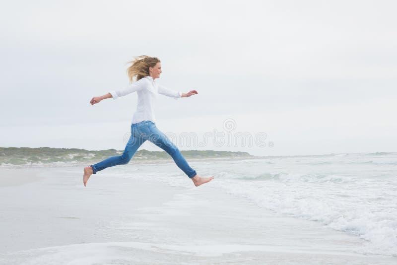 Vista laterale di una donna casuale che salta alla spiaggia fotografie stock