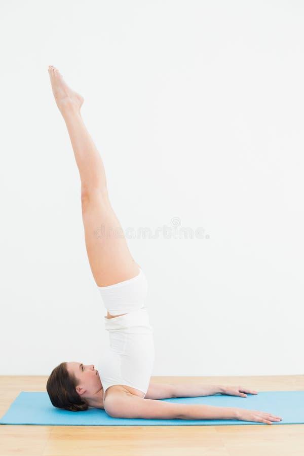 Vista laterale di una donna che allunga le gambe sulla stuoia di esercizio fotografie stock libere da diritti