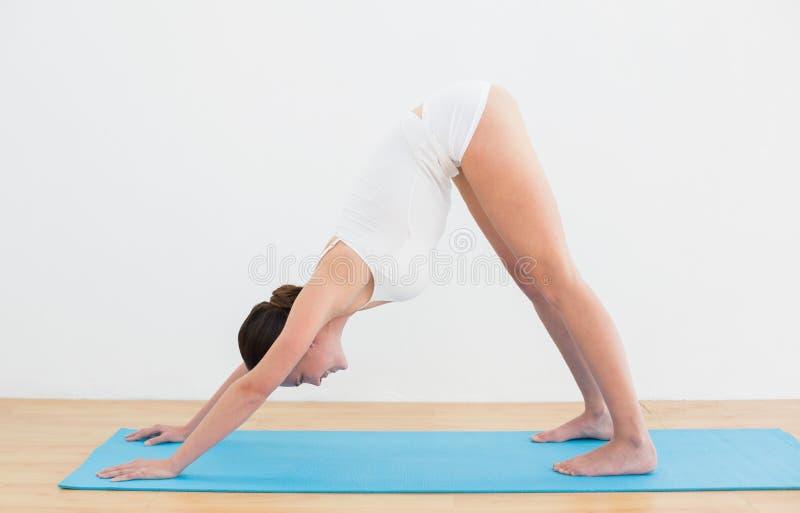 Vista laterale di una donna che si esercita sulla stuoia fotografie stock libere da diritti