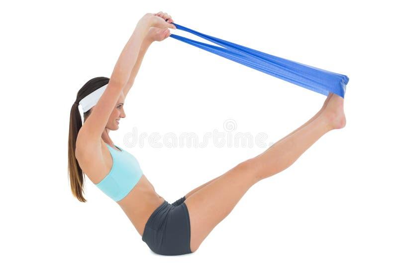 Vista laterale di una donna di misura che si esercita con una cinghia blu di yoga immagini stock