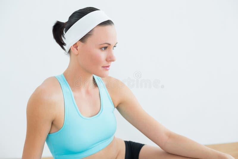 Vista laterale di una donna premurosa nello studio di forma fisica fotografie stock libere da diritti