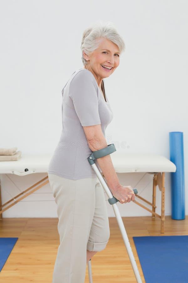Vista laterale di una donna senior sorridente con le grucce immagine stock libera da diritti