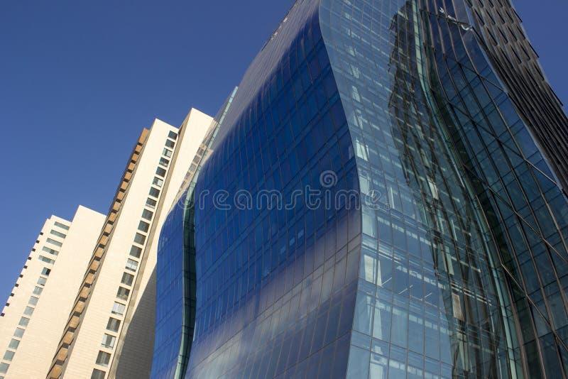 Vista laterale di una parete blu curva della finestra di vetro di una costruzione corporativa moderna ed elegante, accanto a gial immagini stock