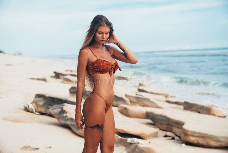 Vista laterale di una posa di modello abbronzata della donna snella su una spiaggia bianca Il tatuaggio sulla gamba sottolinea l' fotografia stock libera da diritti