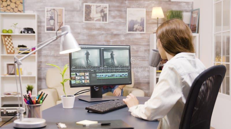Vista laterale di una videografa che lavora nella post-produzione di un film immagini stock