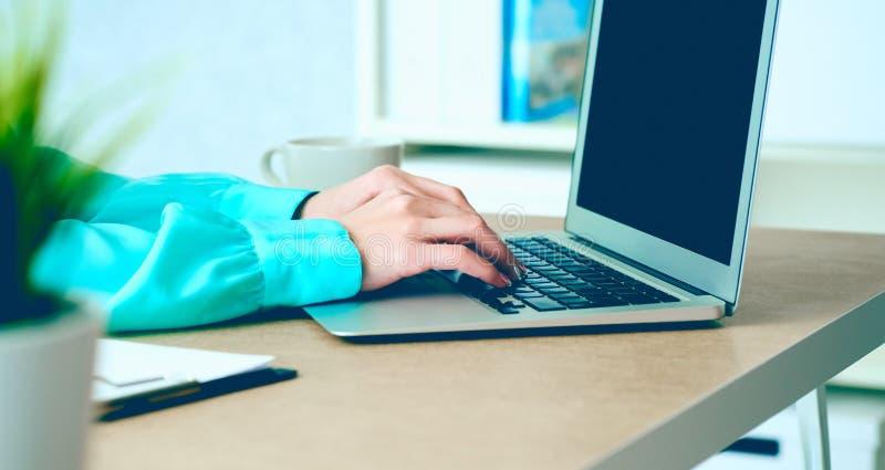 Vista laterale e chiudersi su delle mani della donna che scrivono sulla tastiera del computer portatile nell'interno dell'ufficio immagine stock