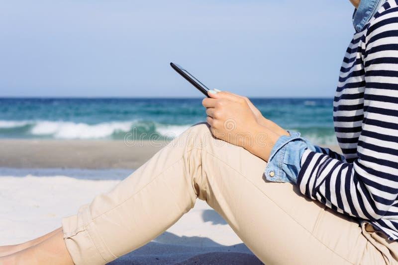 Vista laterale: la donna nella camicia a strisce sulla spiaggia a leggente immagine stock libera da diritti