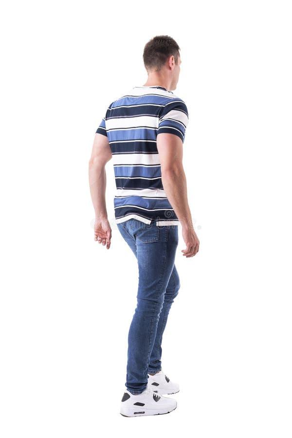 Vista laterale posteriore di giovane uomo adulto casuale che cammina o che lascia distogliere lo sguardo fotografia stock libera da diritti