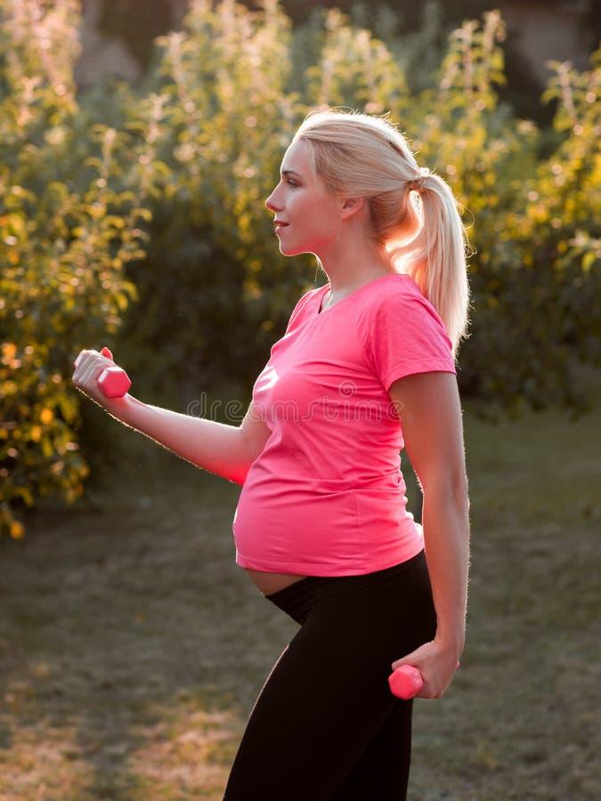 Vista laterale sulla donna incinta con le teste di legno fotografie stock