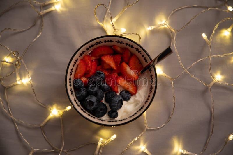 Vista laterale superiore di una ciotola con yogurt, le fragole ed i mirtilli sopra gli strati grigi con le luci immagini stock
