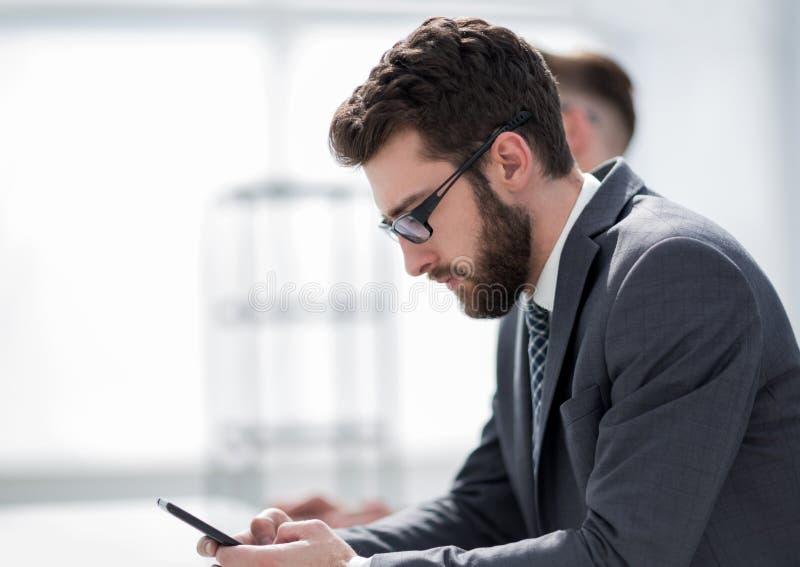 Vista laterale un uomo d'affari bello sta utilizzando uno smartphone immagini stock libere da diritti