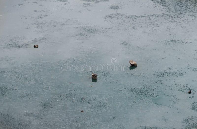 Vista laterale vicino alla riva del mare con piccoli sassolini e pietre lavate Ghiaccio congelato su una pietra Icicle sulla spia immagine stock