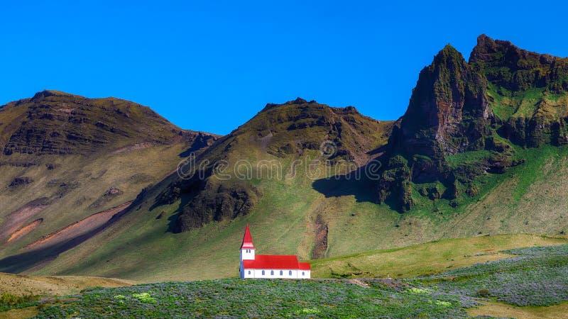 Vista lindo da igreja cristã de Vikurkirkja na frente do mouintaine fotos de stock royalty free