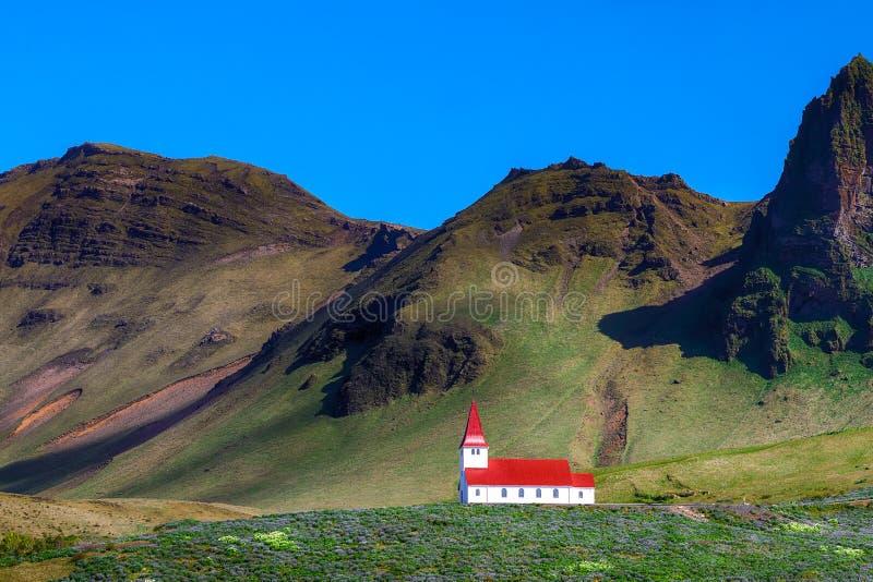 Vista lindo da igreja cristã de Vikurkirkja na frente do mouintaine imagens de stock royalty free