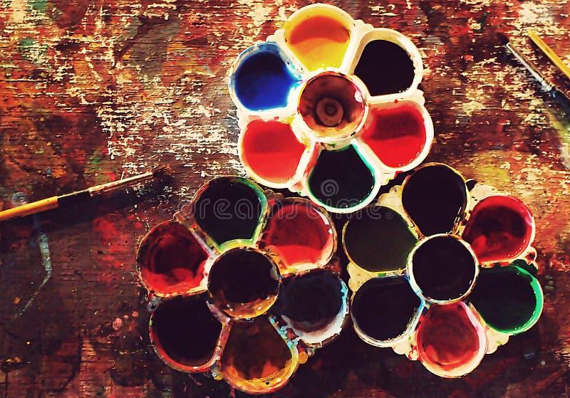 Vista lisa superior da tabela artística suja colorida com paletas de cores e EFEITOS ESPECIAIS da fotografia das escovas de pintu imagens de stock