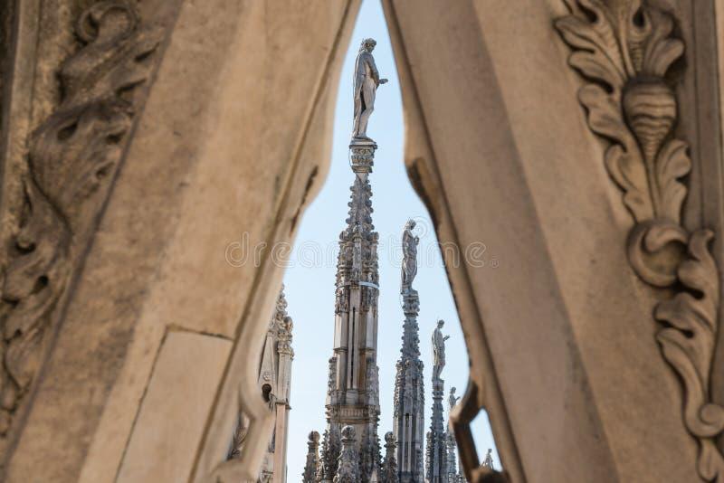 Vista a los chapiteles y a las estatuas en el tejado del Duomo en Milán fotos de archivo