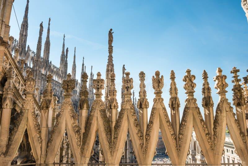 Vista a los chapiteles y a las estatuas en el tejado del Duomo en Mil?n fotos de archivo