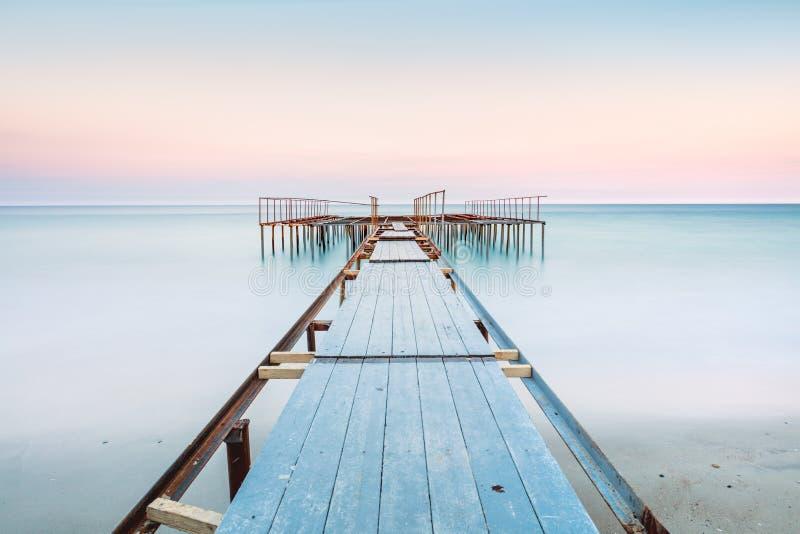 Vista lunga di esposure di vecchio molo in un mare calmo con il cielo delicato, fotografie stock libere da diritti