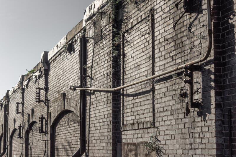 Vista lungo il fronte di una costruzione industriale del magazzino, di vecchio mattone e dei tubi immagini stock