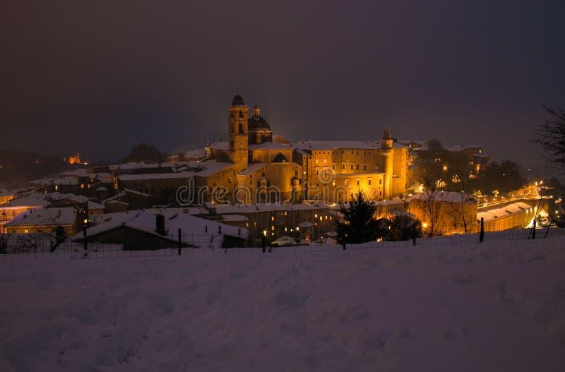 Vista mágica da cidade de Urbino com neve na noite na região de marche, Itália fotos de stock