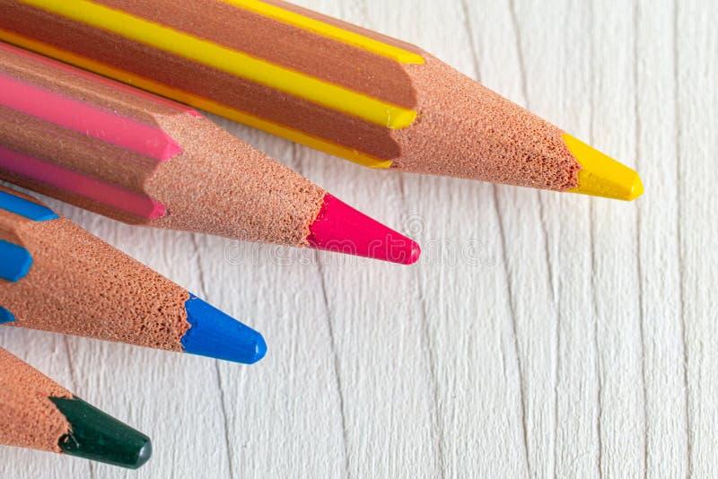Vista macra superior de varios lápices coloreados en el fondo de madera blanco en horizontal fotos de archivo