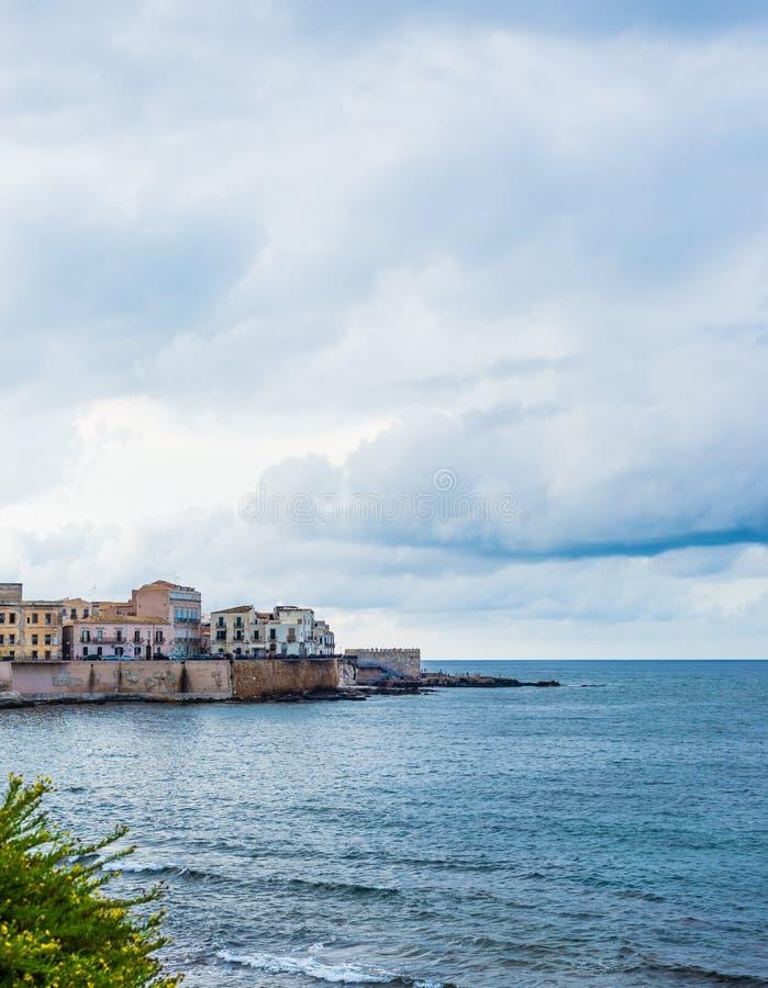 Vista maravilhosa da frente marítima de Ortigia em Siracusa em um dia de verão, com mar azul e o céu nebuloso como um contexto fotos de stock royalty free