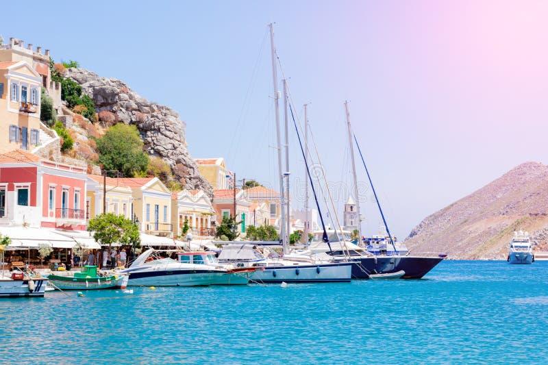 Vista maravilhosa sobre casas coloridas em rochas e barcos à vela no cais do mar azul profundo do Mediterrâneo na ilha grega Symi imagens de stock