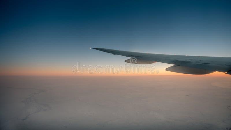 Vista maravillosa del cielo crepuscular a través de la ventana un aeroplano foto de archivo libre de regalías