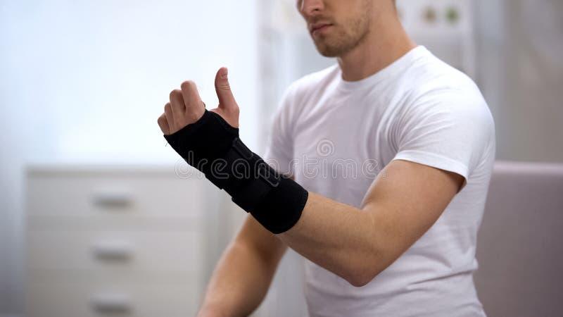 Vista masculina à mão com apoio de pulso do titã, equipamento ortopédico, traumatismo foto de stock royalty free