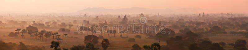 Vista mistica arancio del paesaggio di alba con le siluette di vecchie tempie antiche e palme in nebbia di alba dal pallone fotografie stock