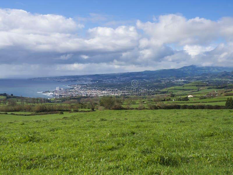 Vista na baía do oceano da cidade de Lagoa com os montes luxúrias da grama verde, os campos e os pastos, céu azul e nuvens branca fotografia de stock