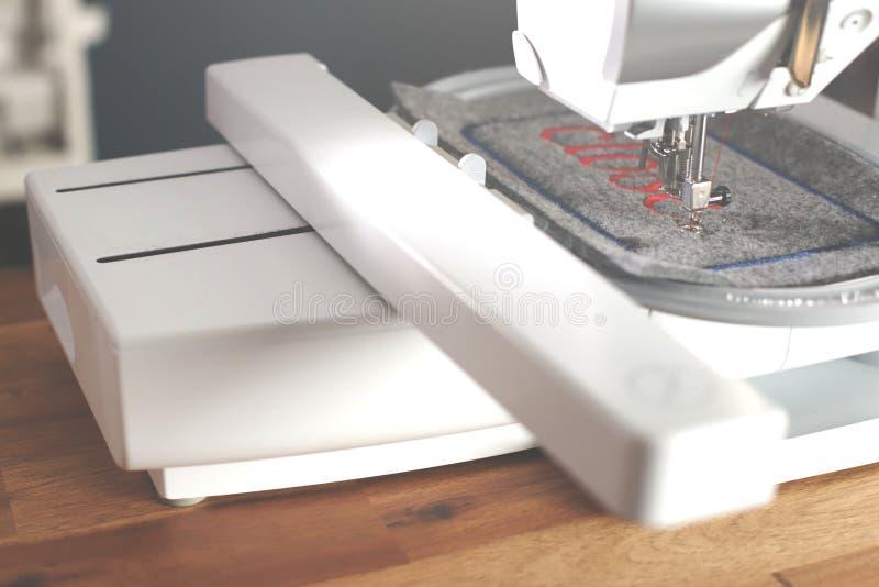 vista na máquina de costura e na unidade do bordado que costuram a rotulação vermelha no feltro em um ambiente à moda do trabalho imagens de stock