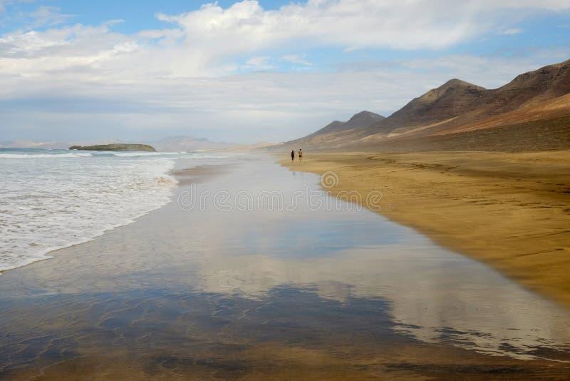 Vista na praia Cofete com as duas pessoas de passeio desconhecidas longe imagens de stock
