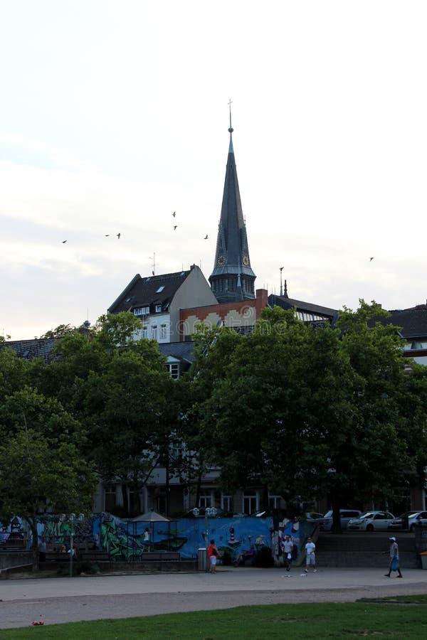 Vista na torre da igreja atrás das árvores no parque em wiesbaden Hessen Alemanha fotografia de stock
