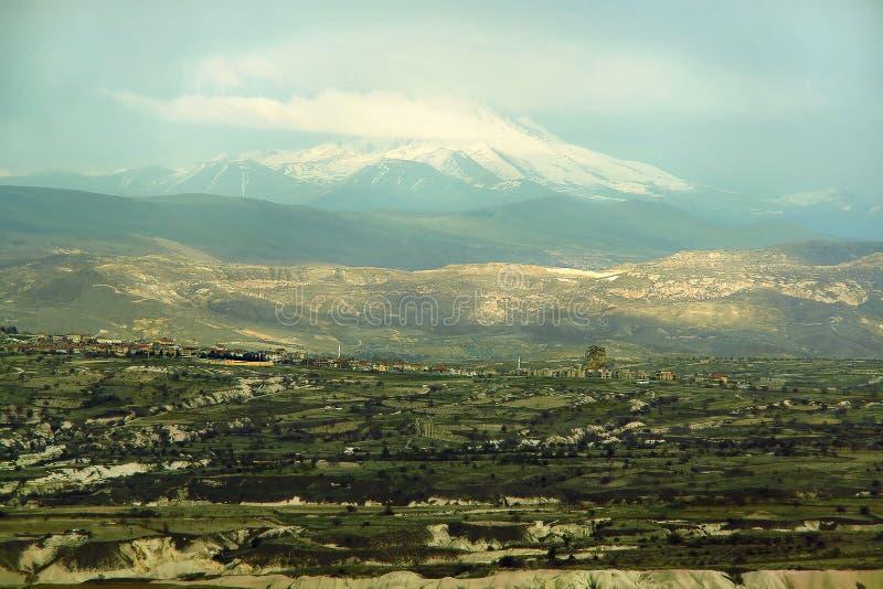 Vista nel campo e nella città contro la montagna Erciyes fotografia stock