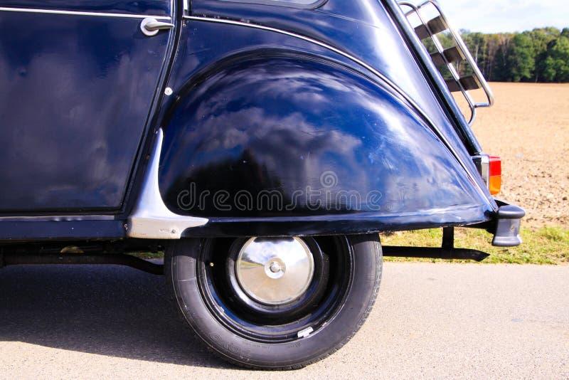 Vista no arco da roda traseira do clássico carro cult francês preto 2CV com mala de madeira na zona rural fotos de stock royalty free