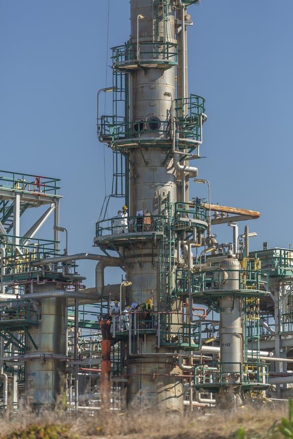 Vista no complexo industrial da refinaria de petróleo e dos povos que trabalham dentro, com construções, equipamento e maquinaria foto de stock