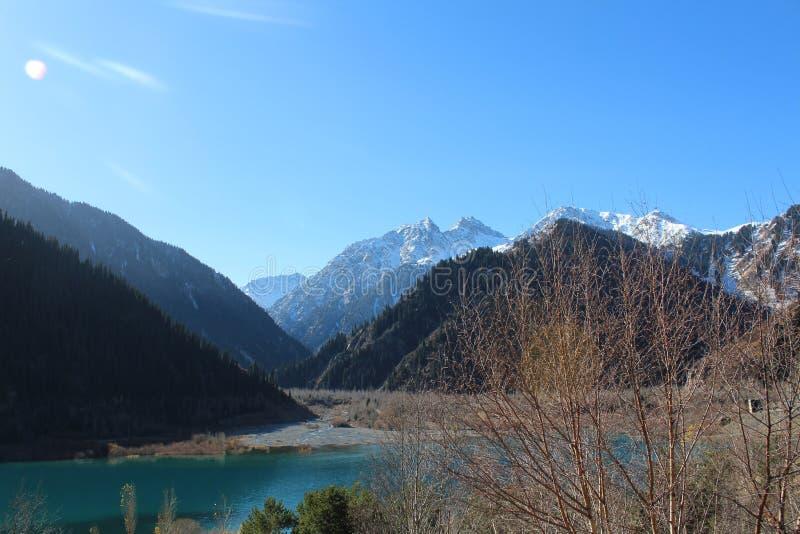 Vista no lago da montanha de Issyk e em picos de montanhas nevado fotografia de stock royalty free